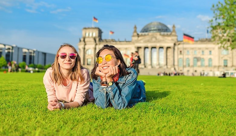 Two young happy girls wearing sun glasses lying on a grass in front of the Bundestag building in Berlin