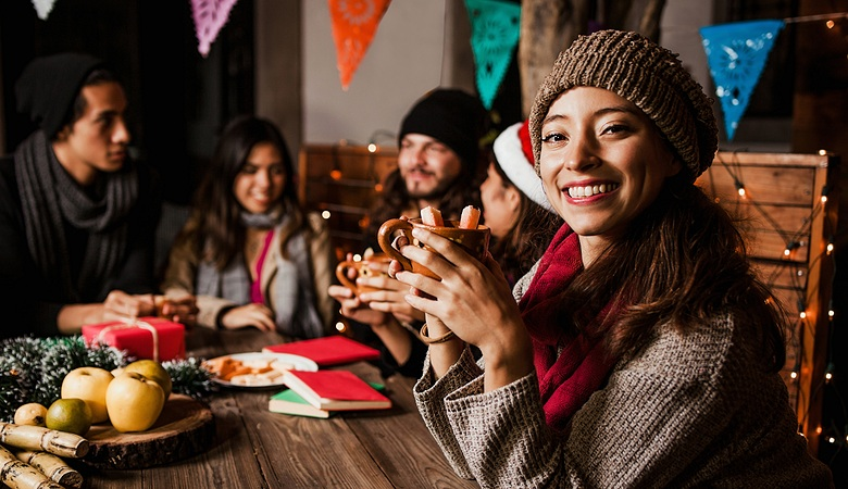 Woman at table with friends at Christmas party in Mexico