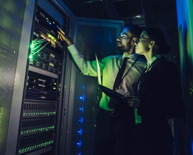 two team members inspecting computer