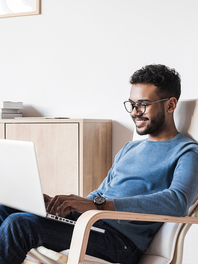 man in chair looking at laptop